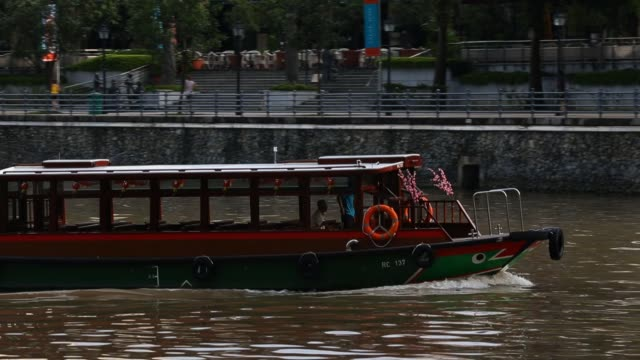 a bumboat makes its way through boat quay on february 20 2013 in singapore bumboats were traditionally used to transport supplies to larger vessels... - river singapore stock videos & royalty-free footage