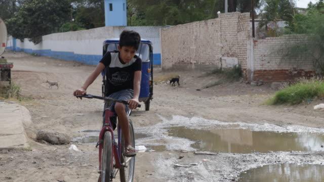 a bumpy road in piura peru a boy is passing by on his bike followed by a rickshaw - bumpy stock videos & royalty-free footage