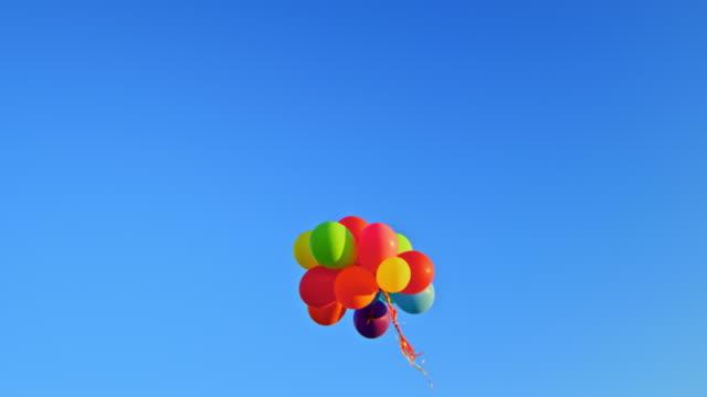 vídeos y material grabado en eventos de stock de slo mo ld un montón de globos de colores flotando a través del cielo azul claro - globo de helio