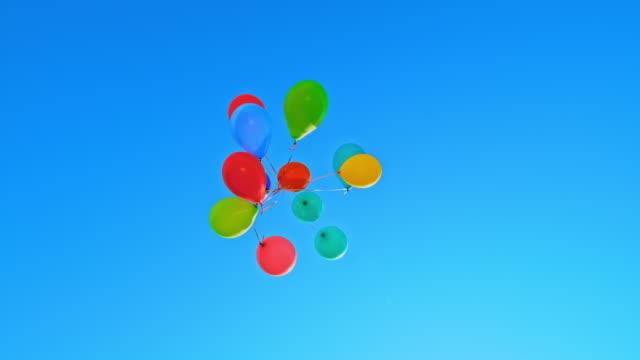 vídeos y material grabado en eventos de stock de slo mo bunch de globos de colores flotando en el cielo soleado azul - globo de helio