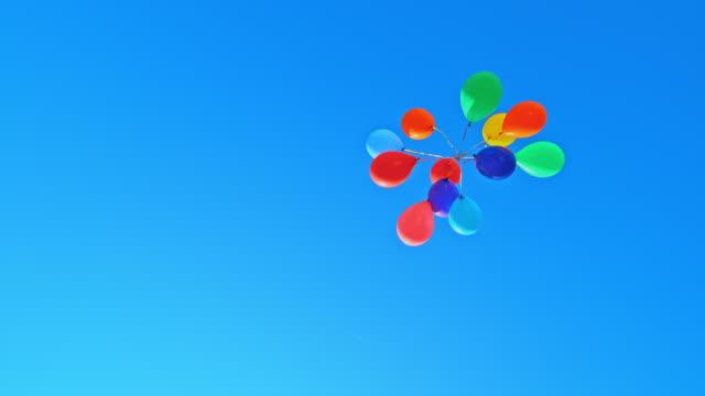 vídeos y material grabado en eventos de stock de slo mo ld montón de globos de colores flotando en el cielo soleado - globo de helio