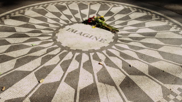 ms ha bunch of flowers laying on mosaic with word 'imagine' in memory of john lennon / new york city, new york state, usa - john lennon stock videos & royalty-free footage