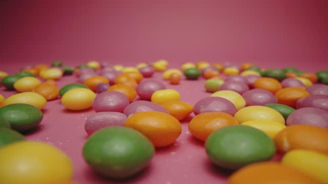 ピンクの背景に多色のゼリービーンズの束 - ジェリービーンズ点の映像素材/bロール