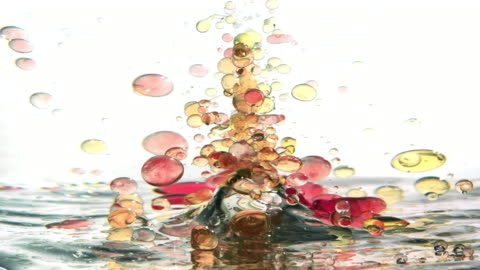 a bunch of red and yellow small oil bubbles creating an underwater tornado upside-down while swirling and twisting - vortex stock videos & royalty-free footage
