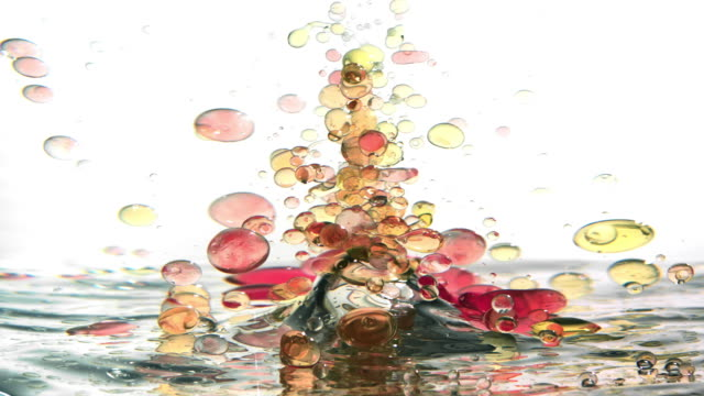 a bunch of red and yellow small oil bubbles creating an underwater tornado upside-down while swirling and twisting - liquid stock videos & royalty-free footage