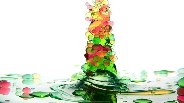 a bunch of red, yellow and green small oil bubbles creating an underwater tornado upside-down while swirling and twisting - essential oil stock videos & royalty-free footage