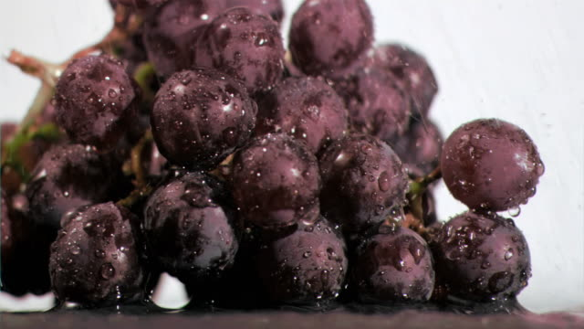 Bunches of grapes in super slow motion being wet
