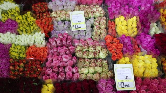 Bunches of roses sit on display at the Rizhsky flower market in Moscow Russia on Friday Aug 28 2015 Shots Customers walk past a stall selling bunches...