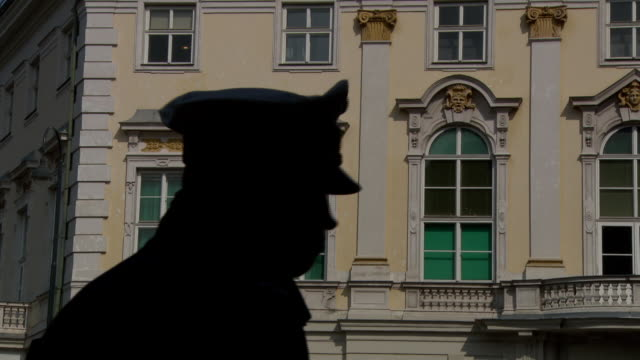 bundeskanzleramt - silhouette of a policeman in front of bundeskanzleramt in vienna - austria video stock e b–roll