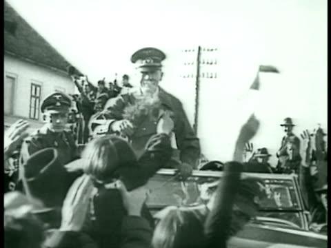 vidéos et rushes de bundesstaat osterreich sign. german nazi troops on horseback walking under arch. hitler riding in car excited crowds hitler taking flowers saluting.... - austria
