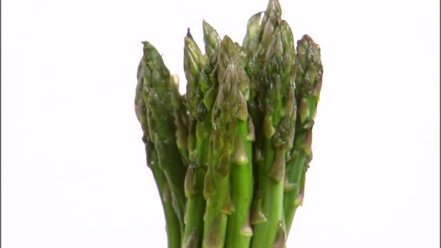 ms zi cu bundle of asparagus rotating against white background / orem, utah, usa - bordsyteinspelning bildbanksvideor och videomaterial från bakom kulisserna