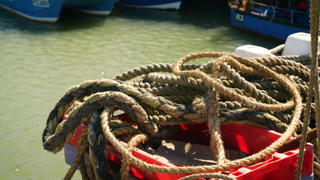 bundle of ropes lie on harbour edge - anchored stock videos & royalty-free footage