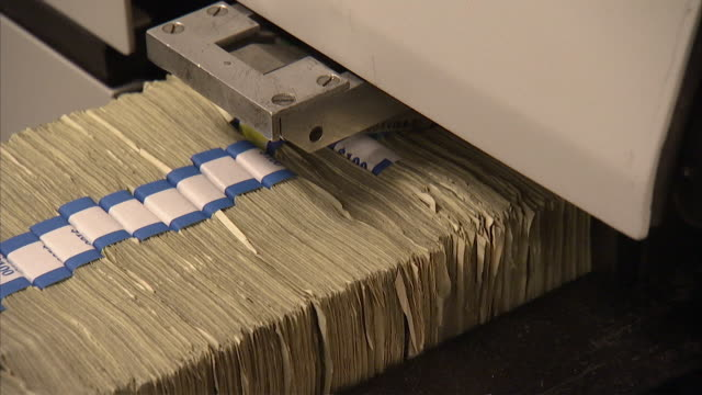 CU Bundles of dollar bills passing through machine along conveyor belt / Kansas City, Kansas, United States