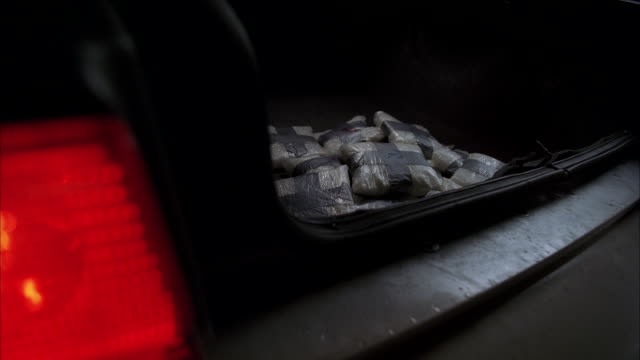 cu bundles of illegal drugs tossed into trunk of  car / unspecified - crime or recreational drug or prison or legal trial video stock e b–roll