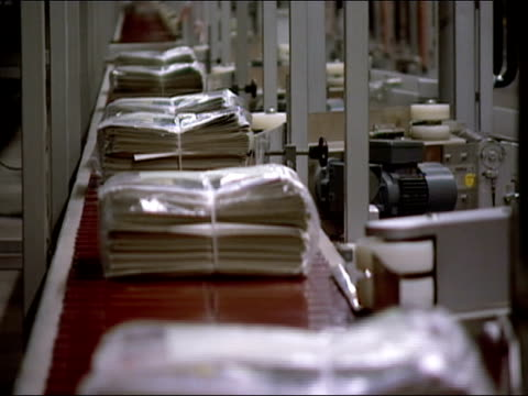 bundles of newspapers wrapped in plastic moving along conveyor belt at newspaper factory - wrapped stock videos & royalty-free footage