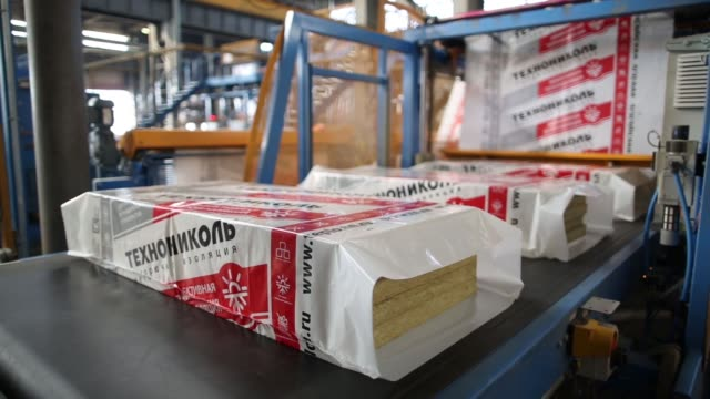 bundles of rock wool thermal insulating slabs are packaged on the production line at the technoplex manufacturing plant, operated by technonicol... - eingewickelt stock-videos und b-roll-filmmaterial