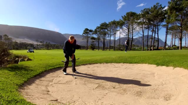 bunker shot onto the green - senior golf swing stock videos & royalty-free footage