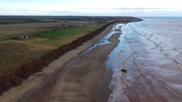 stockvideo's en b-roll-footage met bunker, which used to be situated on top of the cliffs observing the north sea, now lays forlornly on the beach caused by coastal erosion of the... - geërodeerd