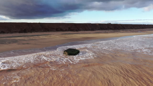 bunker, which used to be situated on top of the cliffs observing the north sea, now lays forlornly on the beach caused by coastal erosion of the... - coastal feature stock videos & royalty-free footage