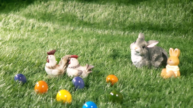 Bunnies, chicks and colored eggs laying on the green grass