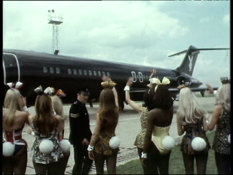 Bunny girls with ears and fluffy tails wave to Hugh Hefner's private plane as it taxis on runway 1970