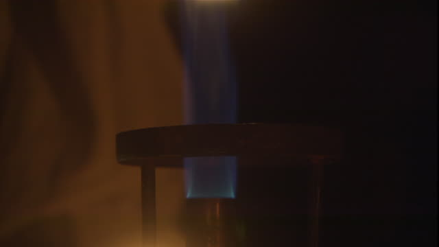 a bunsen burner flame flickers and glows. - bunsen burner stock videos & royalty-free footage