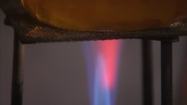 a bunsen burner heats liquid in a glass flask. available in hd. - bunsen burner stock videos & royalty-free footage
