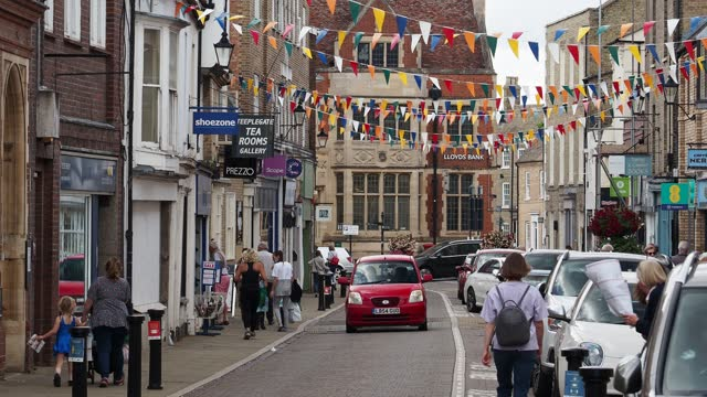bunting on the main shopping street in ely, cambridgeshire, uk. - street name sign stock videos & royalty-free footage
