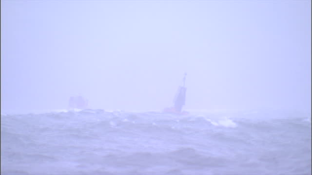 a buoy bobs in storm waves as a ship sails nearby. - buoy stock videos & royalty-free footage