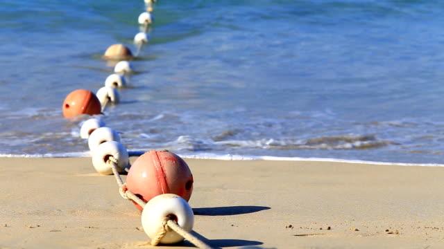 vídeos de stock, filmes e b-roll de boia em mar com ondas fazem a área segura para o turista de natação - boia equipamento marítimo de segurança