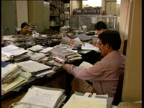 Bureaucrats deal with mountains of paperwork in a Delhi government office