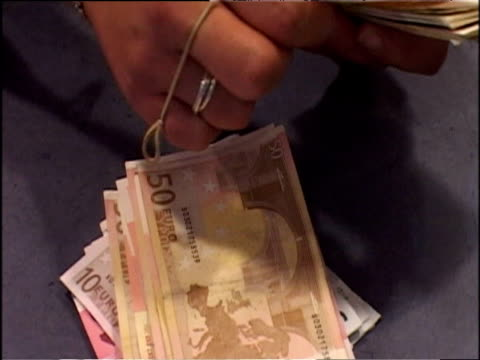 vidéos et rushes de bureaux de change assistant in travel agents cashier counting out euro notes for customer uk - billet de banque euro