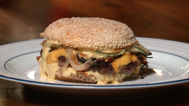 burger with melting cheese and caramelized onions on a plate at chicago restaurant smyth and the loyalist on nov. 23, 2016. - cheeseburger stock videos & royalty-free footage