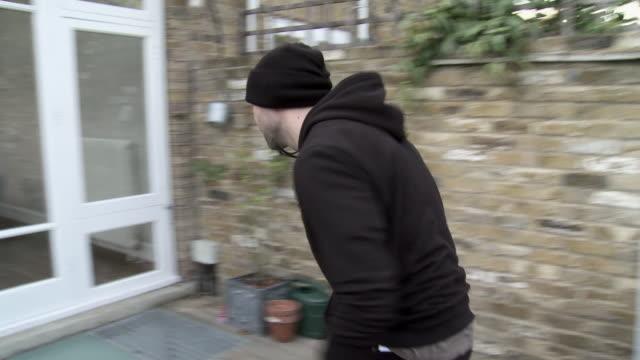 vídeos de stock, filmes e b-roll de burglar breaking into house and stealing laptop - roubando crime