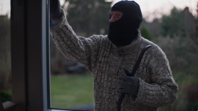 vídeos de stock, filmes e b-roll de arrombador verificando casa - roubando crime