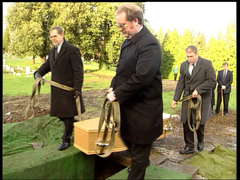 vídeos de stock e filmes b-roll de ms hearse carrying coffin along thru cemetery tms grave prepared for burial tilt up coffin being carried towards ms pallbearers lowering coffin in to... - baixar