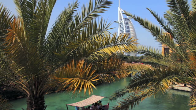 ws burj al arab hotel from souk madinat, palm leaves in foreground / dubai, united arab emirates - palmenblätter stock-videos und b-roll-filmmaterial