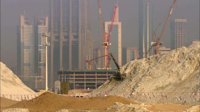 ms burj dubai and skyscrapers under construction, heap of sand in foreground, dubai, united arab emirates - クレーン点の映像素材/bロール