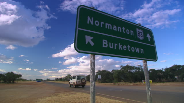 WS Burke town road Sign & car running on road with cloudy sky / Cloncurry, Queensland, Australia