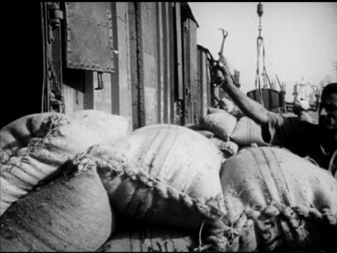 burlap bags of surplus product for export being unloaded from railroad train cars. angled pak mail express' locomotive moving slowly forward along... - 荒い麻布点の映像素材/bロール