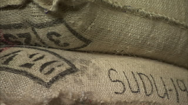 burlap sacks hold coffee beans. - 麻袋点の映像素材/bロール