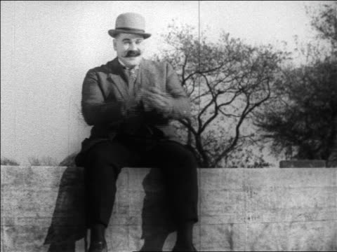 b/w 1925 burly man in hat with mustache sitting on wagon clapping / feature - anno 1925 video stock e b–roll