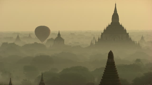 Burma-Myanmar : Hot air balloon over temple in the mist