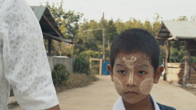 m/s burmese boy with school uniform on the road to school with his mother - schoolboy stock videos and b-roll footage