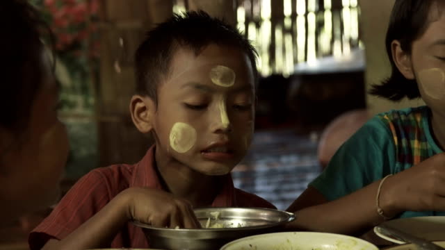 m/s burmese family (siblings) having lunch in a rural home - myanmar stock-videos und b-roll-filmmaterial