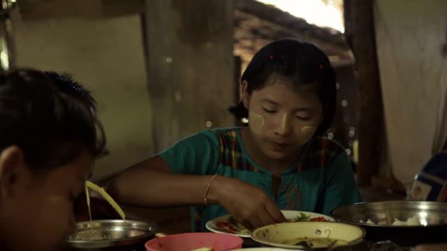 m/s burmese family (siblings) having lunch in a rural home - 団らん点の映像素材/bロール