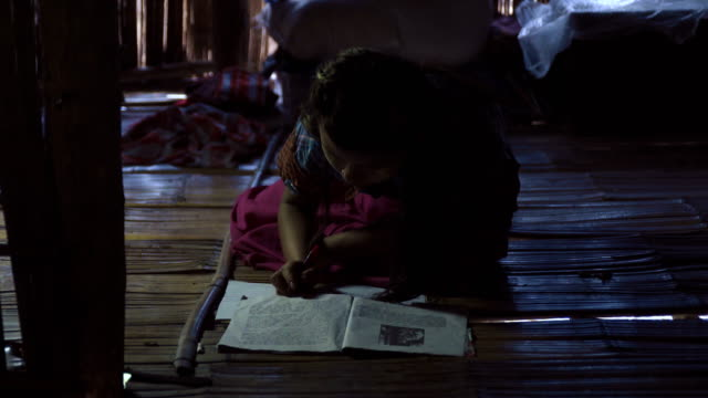 f/s burmese girl doing her homework in the floor, traditional house - myanmar stock-videos und b-roll-filmmaterial