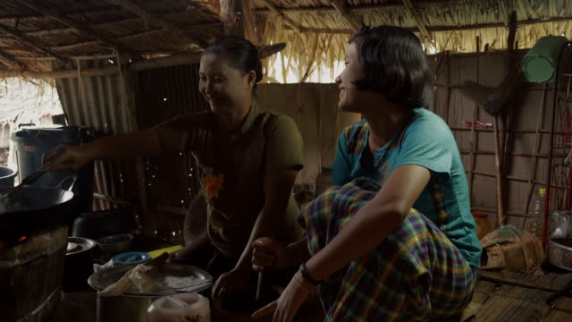 f/s burmese mother and teenage daughter cooking in a traditional house - myanmar stock-videos und b-roll-filmmaterial