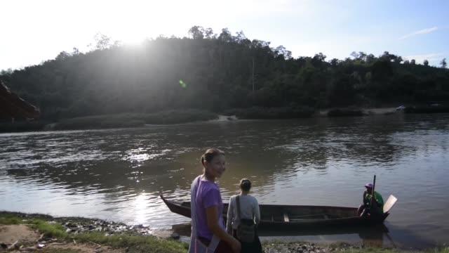 Burmese refugees crossing the border illegally through a river