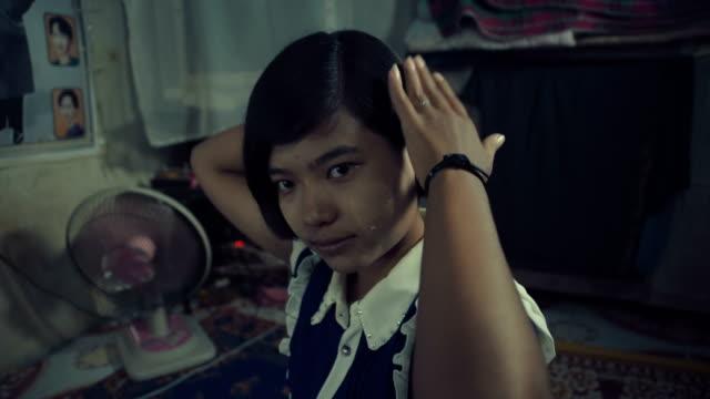M/S Burmese teenage girl brushing her hair in her home